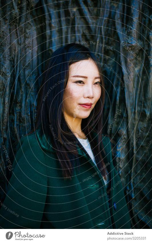 Nachdenkliche Asiatin, die an einer rauen Wand lehnt Frau anlehnen besinnlich Wegsehen Wurzel Baum Straße Großstadt asiatisch urwüchsig Relief Oberfläche