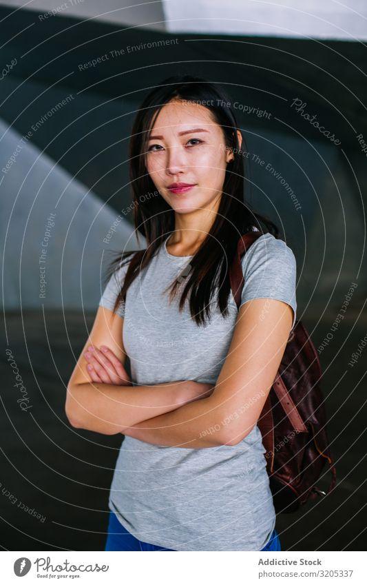 Selbstbewusste asiatische Frau schaut in die Kamera heiter positiv verschränkte Arme Lächeln Stadt lässig Jugendliche Glück U-Bahn Durchgang Großstadt