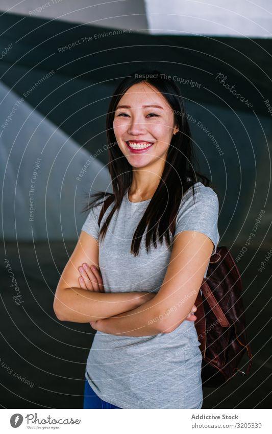 Fröhliche Asiatin schaut in die Kamera Frau heiter positiv verschränkte Arme Lächeln asiatisch Stadt lässig Jugendliche Glück U-Bahn Durchgang Großstadt