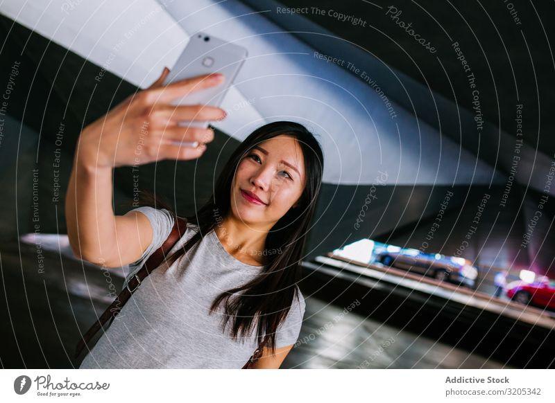 Asiatische Frau nimmt sich in der Untergrundpassage selbst ein Selfie U-Bahn Durchgang Körperhaltung Lächeln asiatisch Jugendliche PDA lässig Stadt schäbig
