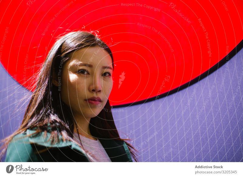 Porträt einer ernsthaften asiatischen Frau hell Wand Stadt Großstadt Straße Jugendliche Farbe urwüchsig Dame Stil trendy Lifestyle Freizeit & Hobby lässig
