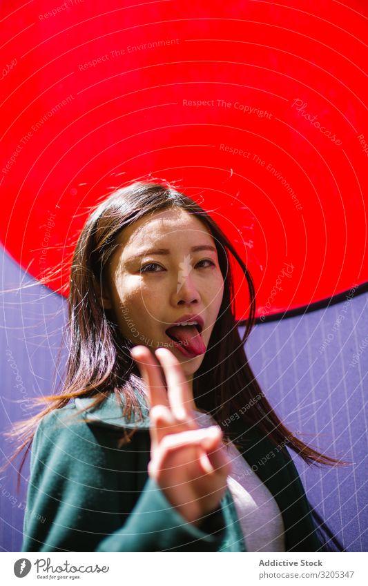 Asiatische Frau mit Zunge und V-Zeichen Zunge zeigen v-Zeichen gestikulieren hell Wand Stadt Großstadt Straße asiatisch Jugendliche lustig zwei Finger Frieden