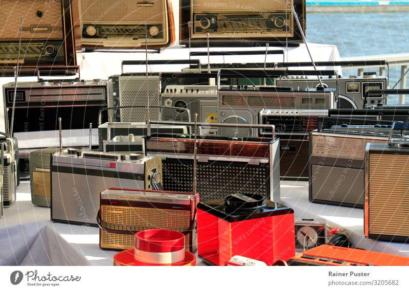 Zahlreiche Radios auf einem Flohmarkt-Tisch sprechen Radiogerät Köln Flohmarktstand alt eckig retro mehrfarbig schwarz Nostalgie altehrwürdig Farbfoto