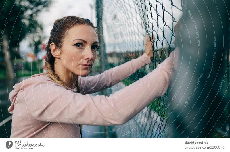 Sportliches Mädchen auf dem Sportplatzzaun ruhend Lifestyle schön Körper Freizeit & Hobby Mensch Frau Erwachsene Wolken Regen Fitness authentisch selbstbewußt