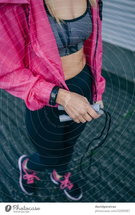 Junge Frau mit Sportbekleidung und Springseil Lifestyle Stil Körperpflege Gesundheitswesen Freizeit & Hobby Mensch Erwachsene Turnschuh Fitness springen