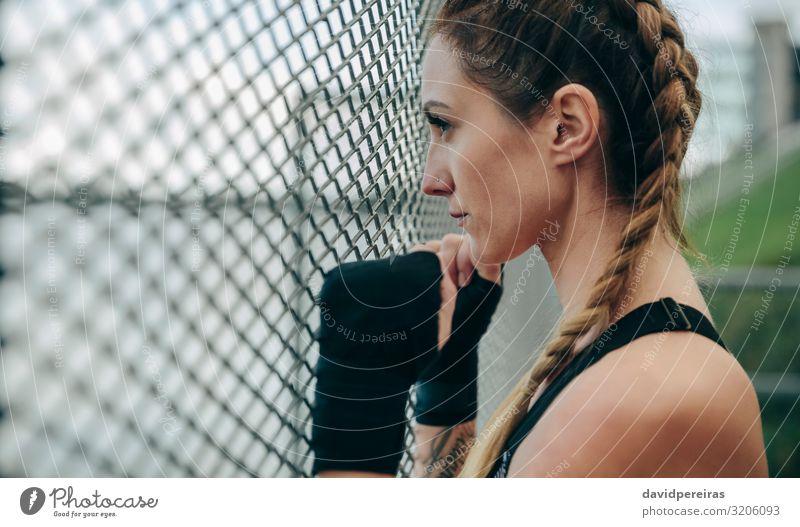 Sportlerin, die durch einen Zaun schaut. Lifestyle schön Körper Gesicht Freizeit & Hobby Mensch Frau Erwachsene Hand Wolken Handschuhe Fitness authentisch stark