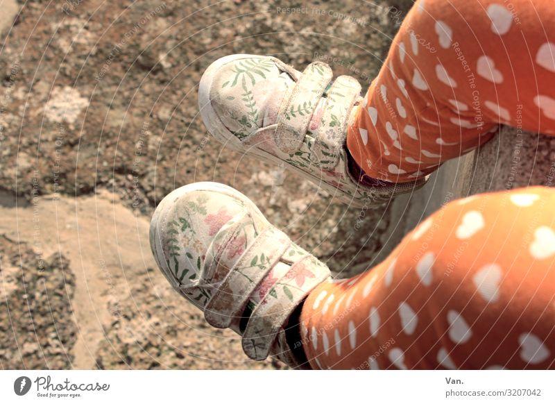 Walking in my shoes Kind Mädchen Beine Fuß 1 Mensch Mauer Wand Hose Schuhe sitzen orange Herz geblümt Muster Stein Boden Farbfoto Gedeckte Farben Außenaufnahme