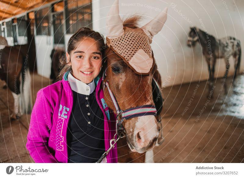 Mädchen mit entzückendem Pony mit Hut Ponys Pferdestall Tier in die Kamera schauen Kind Porträt Umarmen Freund Haustier Kindheit Landschaft Kraulen wenig