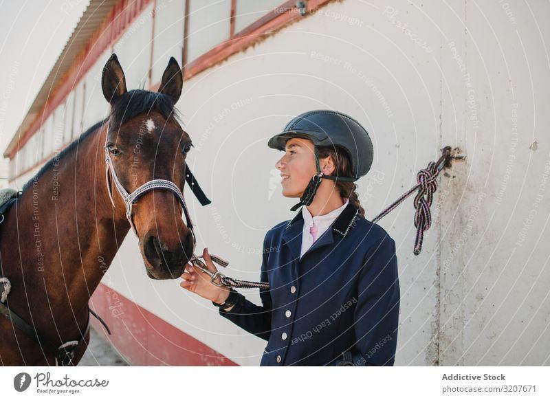 Frau im Jockey-Outfit mit Pferd stehend Kraulen Tier Reiterin Teenager jung Haustier Freund Liebe Streicheln Schutzhelm berühren schön Pflege Säugetier