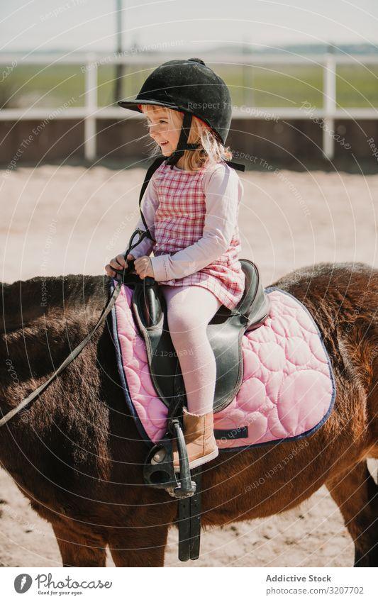 Kleines glückliches Mädchen reitet Pferd auf dem Hippodrom Lächeln Sport Mitfahrgelegenheit Porträt Reiterin Kind üben Kindheit wenig Jockey ländlich Glück Tier