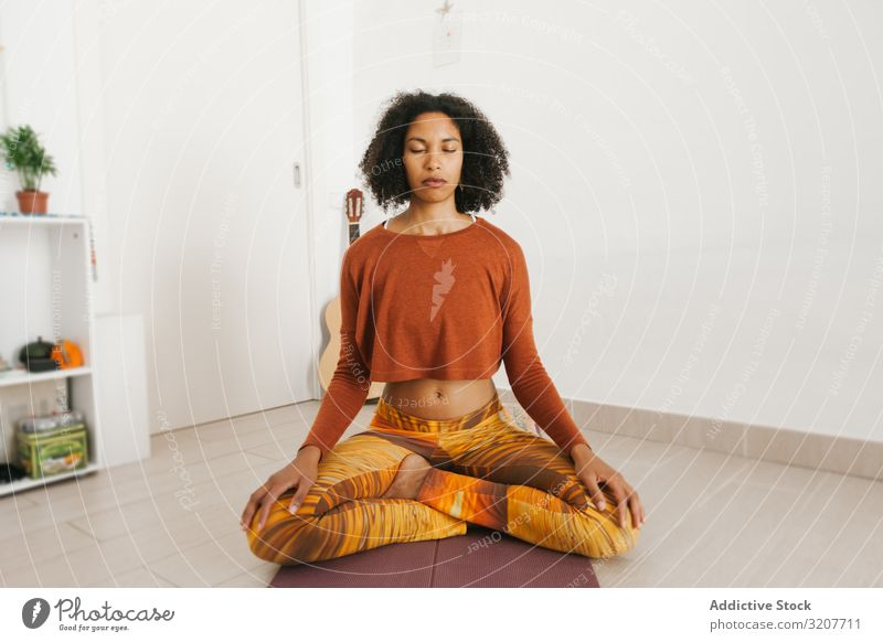 Sportliche Frau sitzt in Yoga-Position mit geschlossenen Augen Meditation praktizieren positionieren Sitzen Erholung Übung schön Fitness Freizeit Lotos Training