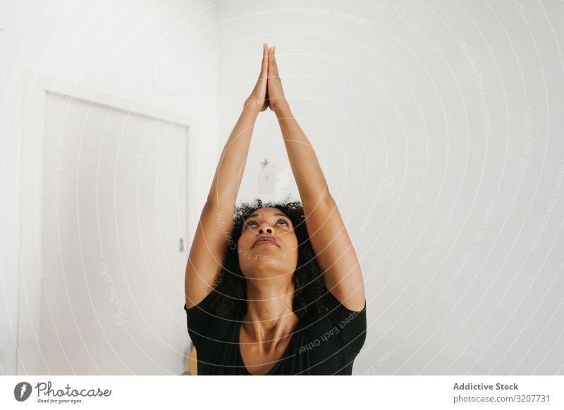Sportliche Frau steht in Yoga-Position und streckt die Arme praktizieren positionieren Erholung Übung gedehnt Hände schön Fitness Freizeit Training meditieren