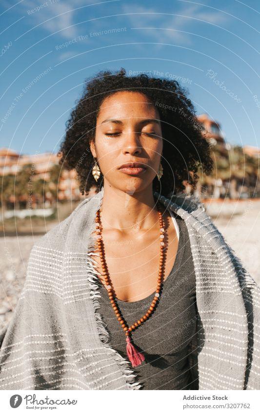 Sportliche Frau sitzt am Sandstrand in Asana meditierend praktizieren Yoga positionieren Sitzen Erholung Übung schön Fitness Freizeit Training Wellness Energie