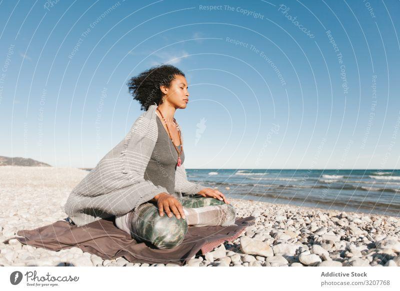 Sportliche Frau sitzt am Sandstrand in Asana meditierend praktizieren Yoga positionieren Sitzen Erholung Übung schön Fitness Freizeit Training Wellness schlank