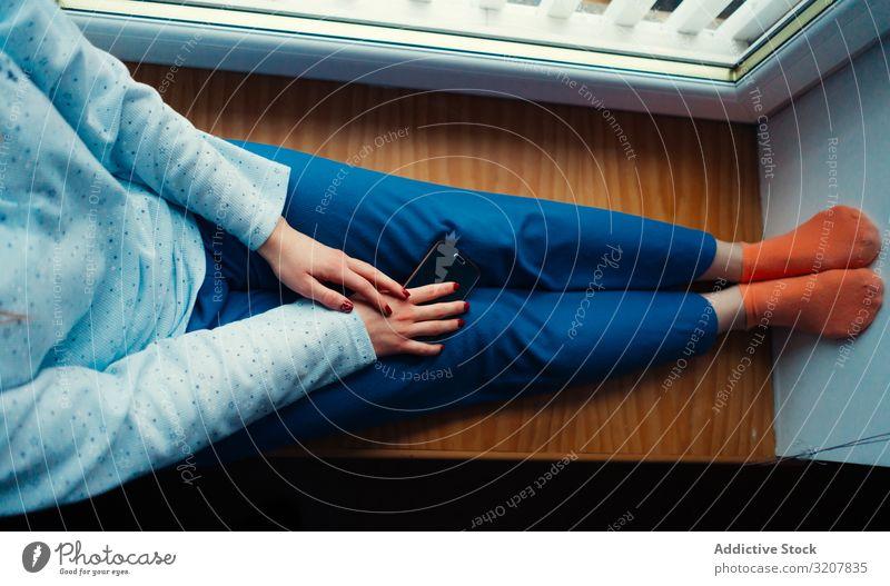 Getreidefrau in Hauskleidung auf dem Fensterbrett Frau Komfort heimwärts gemütlich Smartphone farbenfroh Schottland Sitzen sich[Akk] entspannen Lifestyle