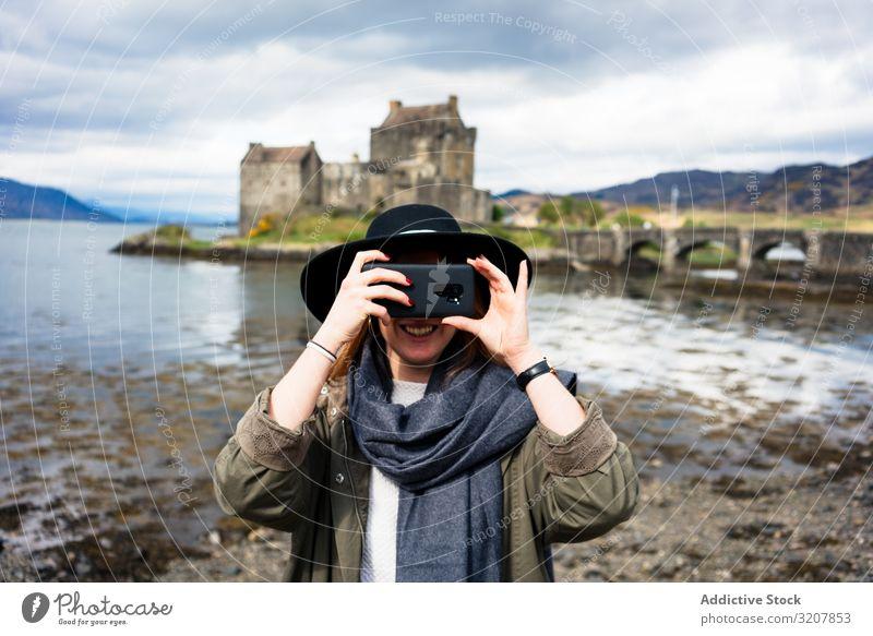 Lächelnde, reisende Frau beim Fotografieren mit dem Telefon Schottland fotografierend Smartphone Natur gealtert Burg oder Schloss Kosten See trendy benutzend