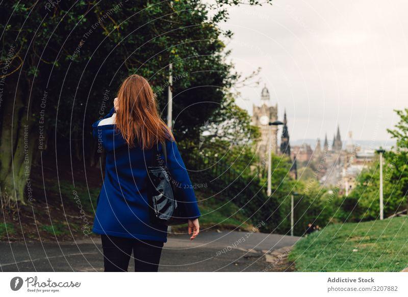 Frau, die in einem Park spazieren geht Baum Kofferraum Garten idyllisch Dame Windstille ruhig Gelassenheit friedlich tagsüber horizontal im Freien Reise
