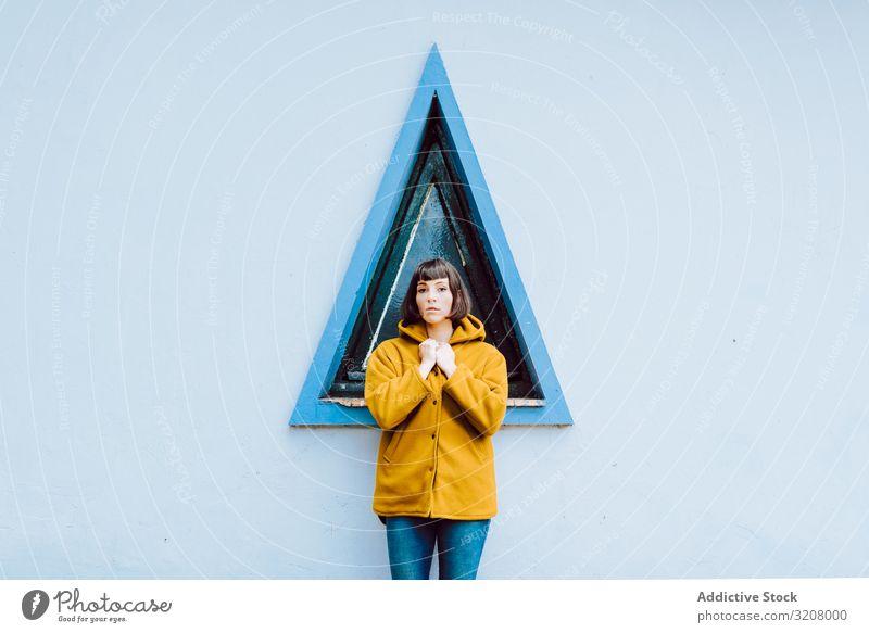 Fröhliche Frau in der Nähe des Dreiecksfensters Lächeln Fenster Gebäude Wand grau jung Glück Stehen Mantel lässig Jacke warm heiter Freude Außenseite