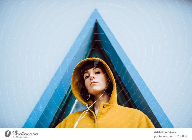 Fröhliche Frau in der Nähe des Dreiecksfensters beim Hören der Musik Lächeln Fenster Gebäude Wand grau jung Glück Stehen Mantel lässig Jacke warm heiter Freude
