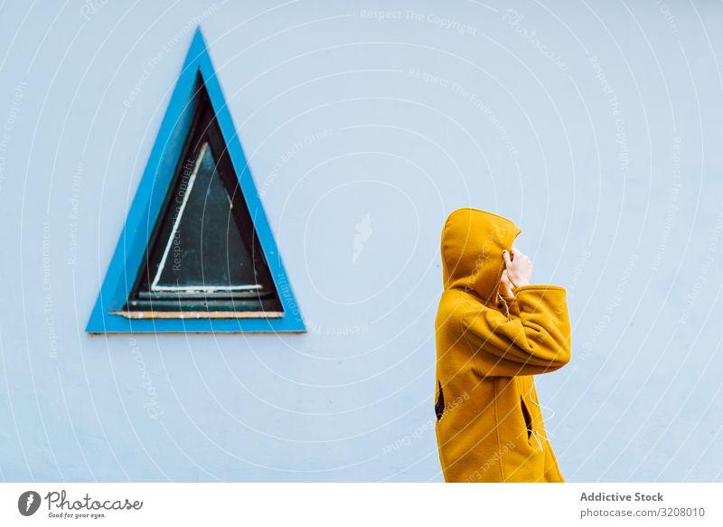 Anonyme Frau beim Verstellen der Motorhaube in der Nähe des Dreiecksfensters ausrichten Kapuze Fenster Gebäude Wand grau jung Stehen lässig Jacke ziehen warm