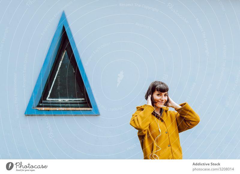 Lächelnde Frau, die in der Nähe des Dreiecksfensters Musik hört zuhören Fenster Gebäude Wand grau berühren Behaarung jung Glück Stehen lässig Jacke warm heiter