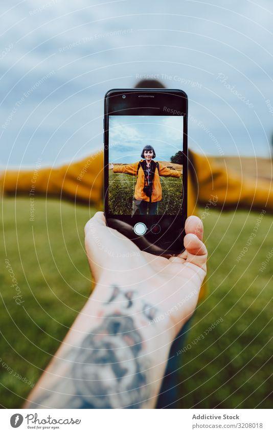 Handaufnahme einer Frau auf dem Feld Foto Smartphone Tattoo ausgestreckte Arme Freiheit Lifestyle Freizeit reisen Ausflug Reise Wochenende Mobile Telefon