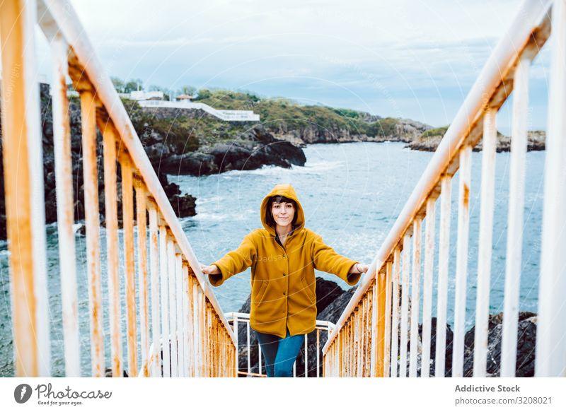 Frau steht auf Stufen in der Nähe des Meeres MEER Ufer Treppenhaus Bucht Wellen Wasser rostig Reling reisen Ausflug Tourismus Reise lässig Küste Unwetter Wetter