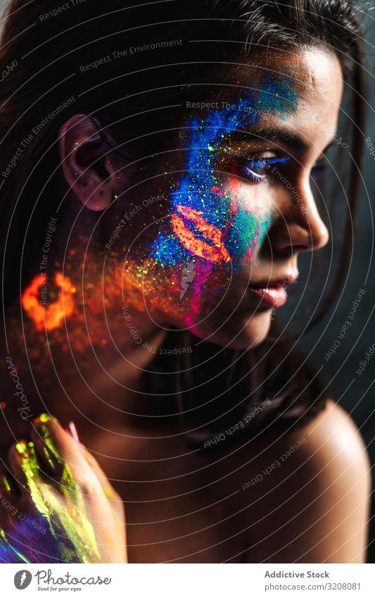 Junge Frau mit UV-Malerei bedeckt jung hübsch Farbe orange Feuer Schwarzlicht fluoreszierend leuchtend uv Lumineszenz Körperkunst Leidenschaft Körpermalerei