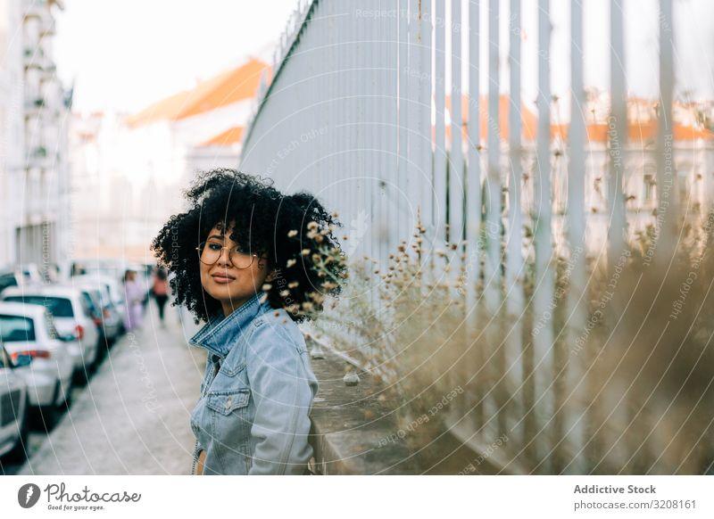 Glückliche ethnische Frau am Metallzaun Mode Freizeit Zaun stylisch trendy glamourös Jeans Jacke Frisur jung Afroamerikaner lässig attraktiv schön hübsch heiter