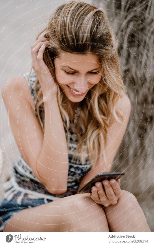 Hübsche Frau benutzt Smartphone am Strand benutzend Sommer Urlaub reisen Mitteilung Erholung Feiertag Resort jung Person attraktiv schön glamourös blond lässig