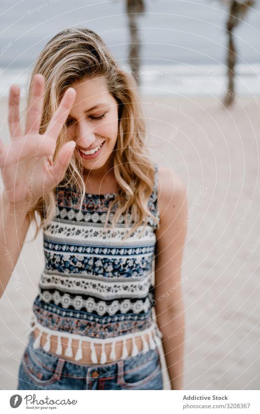 Glückliche Frau posiert am Sandstrand deckend Gesicht Hand Strand Fröhlichkeit Sperrfläche modisch glamourös Sommer Urlaub Feiertag jung Person attraktiv schön