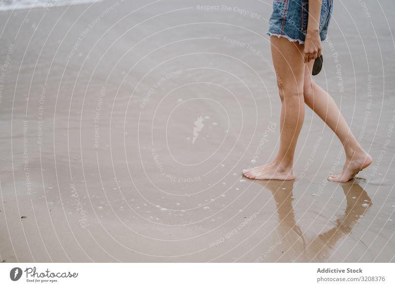 Junge Frau läuft barfuss auf nassem Sand Strand Barfuß Sommer Urlaub reisen Erholung Feiertag Freude Freiheit Fröhlichkeit jung Person attraktiv lässig