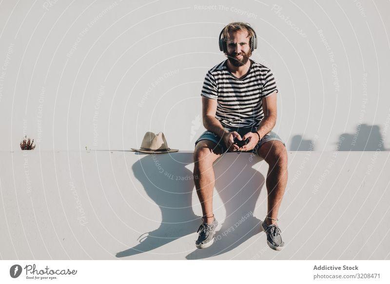 Junger Mann sitzt mit Smartphone und Kopfhörern Musik reisen Urlaub Feiertag la restinga Kanarische Insel El Hierro benutzend Sommer jung männlich Person lässig