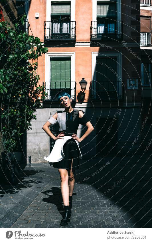 Selbstbewusste Frau in futuristischer Kleidung auf der Straße Großstadt trendy Model Kontrast selbstbewusst Gebäude Straßenbelag Hände an der Taille jung Stil
