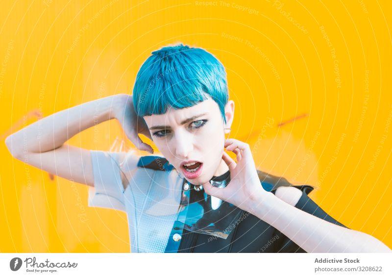 Alternatives Modell-Portrait gegen gelbe Wand Frau futuristisch alternativ Kleid blaue Haare informell Straßenbelag Glamour Dame jung Ausdruck Schönheit Gebäude