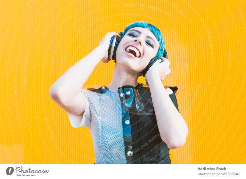 Coole informelle Frau mit Kopfhörern auf der Straße Musik Smartphone Generation heiter Ausdruck pulsierend urban hören futuristisch Subkultur Melodie Lächeln