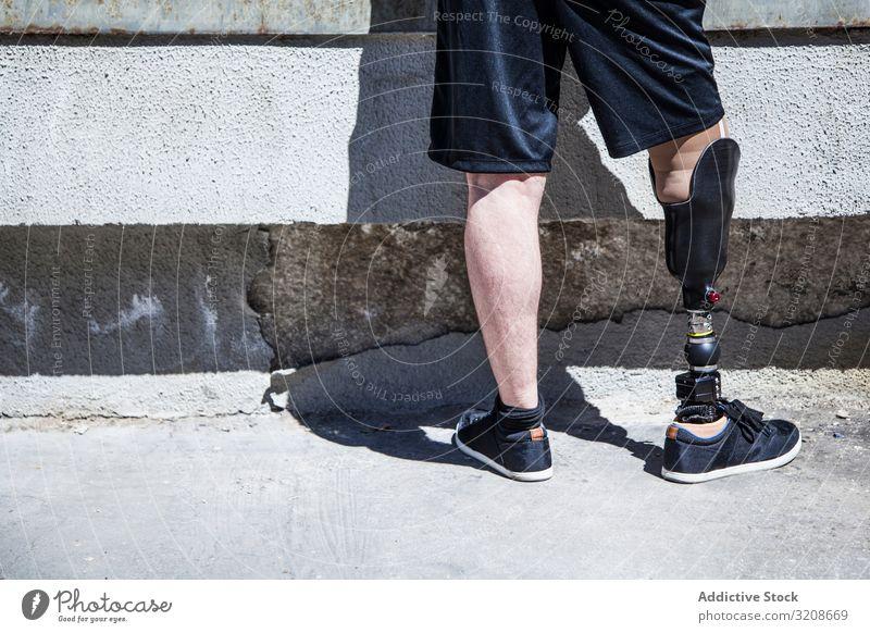 Nicht erkennbarer junger Mann, der mit seiner Beinprothese amputiert wurde Ausdruck deaktivieren männlich Behinderte sitzen Prothesen junger Erwachsener