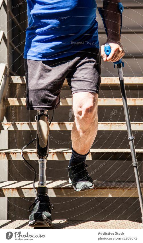 nicht erkennbarer, mit Krücken amputierter Mann, der seine neue Beinprothese testet Ausdruck deaktivieren männlich Behinderte sitzen Prothesen