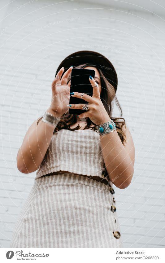 Frau mit Hut lächelt beim Surfen auf dem Smartphone charmant attraktiv jung schön Glück Browsen benutzend Lifestyle Handy lässig Boho Texten heiter Mitteilung