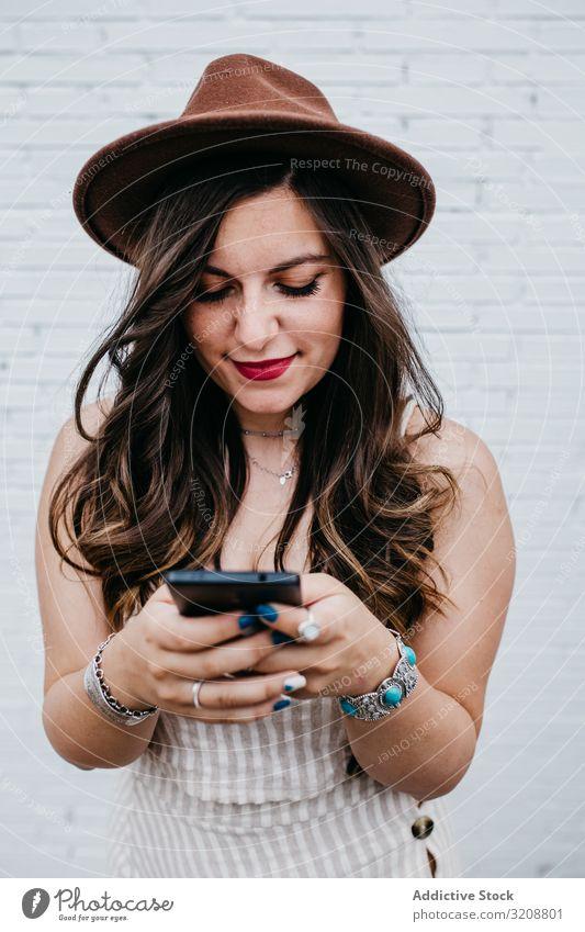 Frau mit Hut lächelt beim Surfen auf dem Smartphone charmant attraktiv jung schön Glück Handy Browsen benutzend Lifestyle lässig Boho Texten heiter Mitteilung