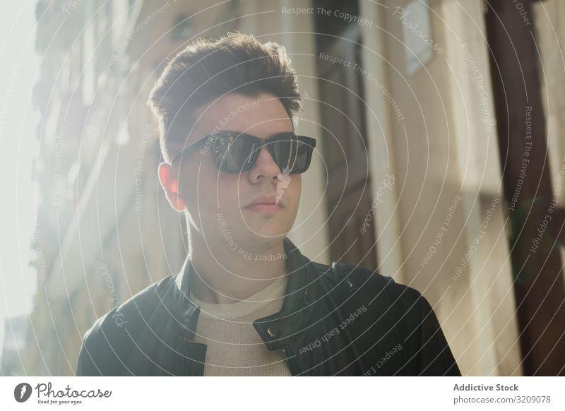 Lächelnder trendiger Mann mit Sonnenbrille gutaussehend Sonnenlicht Sommer Freiheit Fröhlichkeit Straße Frisur Freizeit außerhalb heiter Stehen Träumer Ausdruck