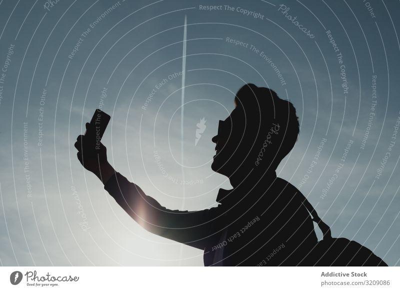 Silhouette eines Mannes mit Telefon gegen den Himmel Selfie tausendjährig Smartphone Technik & Technologie Mobile männlich modern Sonnenlicht hell sorgenfrei