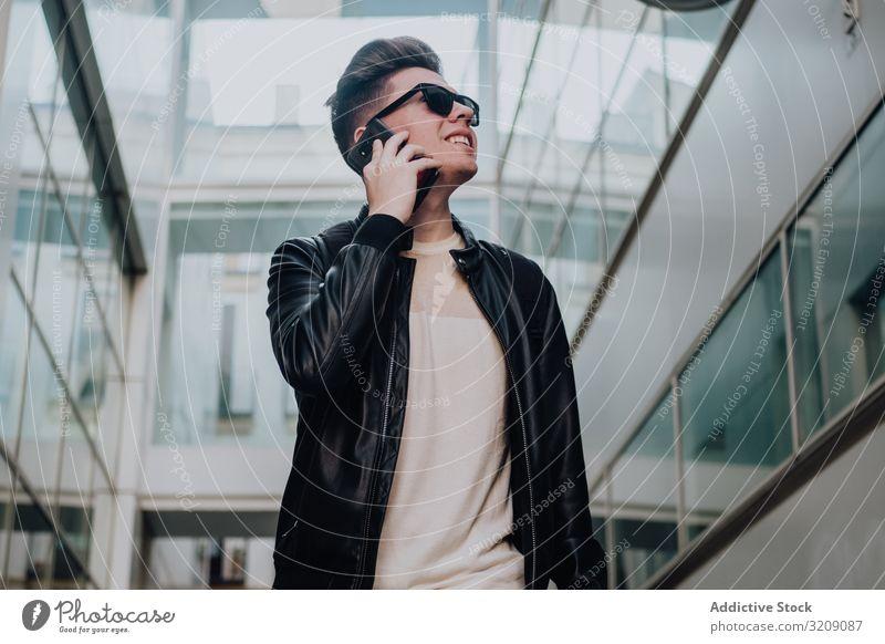 Mann mit Smartphone auf der Straße benutzend Großstadt Lächeln sonnig tagsüber Glück jung gestylt Freizeit Lifestyle Technik & Technologie Gerät Apparatur