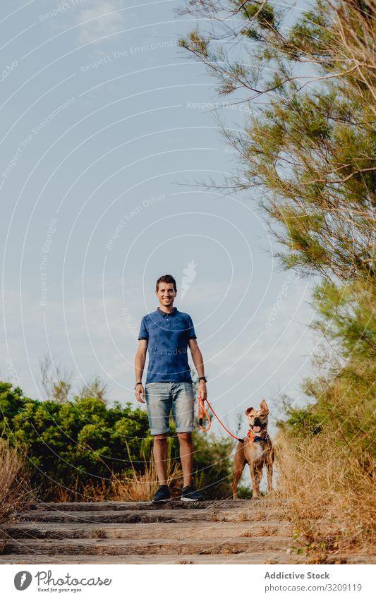 Glücklicher erwachsener Mann, der mit seinem Hund auf dem Land spazieren geht Spaziergang lässig Weg heiter anleinen braun ländlich Landschaft hölzern Baum Grün