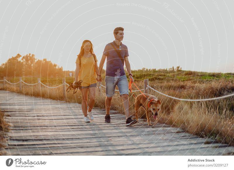 Lässiges erwachsenes Ehepaar geht mit Hund auf einem ländlichen Weg Paar Spaziergang modern lässig Landschaft spielerisch strahlte anleinen braun