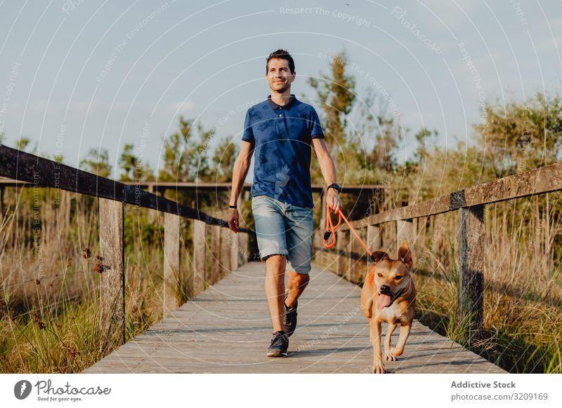 Glücklicher erwachsener Mann geht mit Hund durch die Landschaft laufen lässig heiter anleinen braun ländlich hölzern Baum Grün Tageslicht Haustier Zusammensein