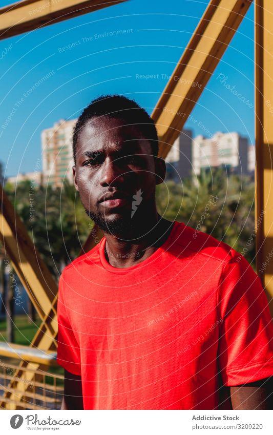Afroamerikanischer Sportler beim Gehen auf einer Brücke Mann aktiv schwarz Afroamerikaner jung Gesundheit Training ethnisch Himmel Läufer Lifestyle Körper