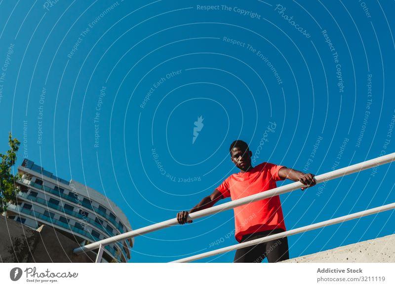 Afroamerikanischer junger Mann auf Brücke unter blauem Himmel urban sportlich Inspiration entschlossen Gesundheit muskulös Blauer Himmel ethnisch schwarz