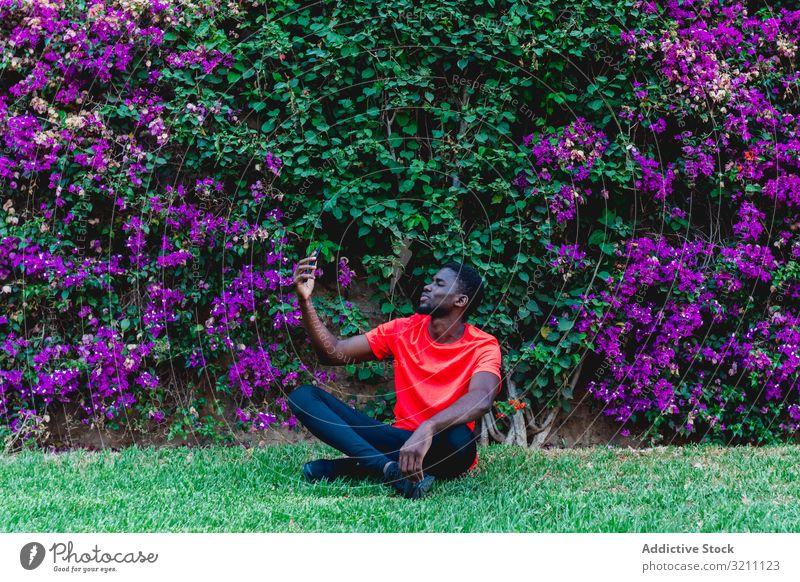 Sportlicher schwarzer Sportler auf dem Handy Mann jung Gesundheit Tageslicht ethnisch ruhen Mitteilung Smartphone Technik & Technologie Afroamerikaner Apparatur