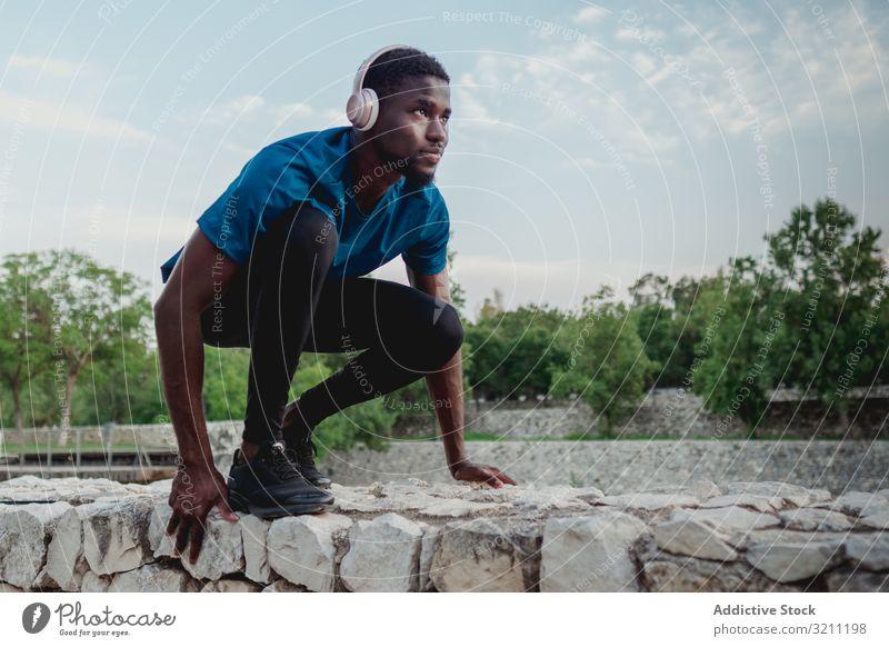 Schwarzer fokussierter Sportler in der Hocke wartend Mann Kauerstart Kopfhörer Gesundheit entschlossen Läufer Freiheit muskulös Training stark